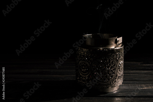 Close up. Vintage silver candlestick with extinguished candle, a trickle of gray smoke. Low key. Black background. Copy space.