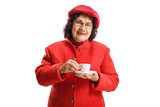 Elderly woman in a red coat standing and drinking an espresso coffee - 243883494