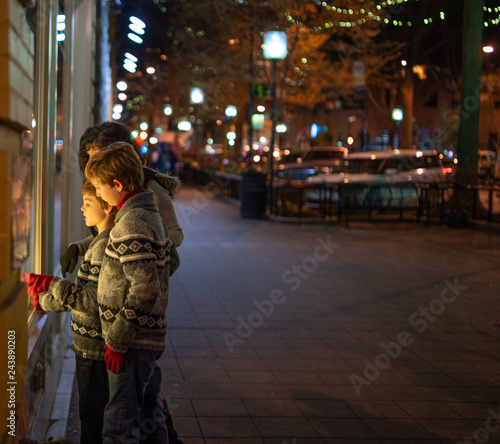 Wall mural Mother and boys window Christmas Shopping in town at night
