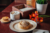 Round cinnamon bun in a plate on a dark wooden table in a cafe - 243904689