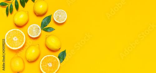 Leinwandbild Motiv Ripe juicy lemons, orange and green leaves on bright yellow background. Lemon fruit, citrus minimal concept, vitamin C. Creative summer minimalistic background. Flat lay, top view, copy space.