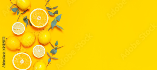 Ripe juicy lemons, orange and green eucalyptus twigs on bright yellow background. Lemon fruit, citrus minimal concept, vitamin C. Creative summer minimalistic background. Flat lay, top view copy space - 243911411