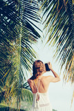 Young blond woman on vacation with smartphone on the beach. - 243942428
