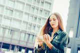 Young blond woman with smartphone in front of skyscrapers - 243944809