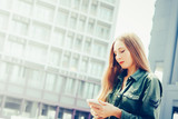 Young blond woman with smartphone in front of skyscrapers - 243944836