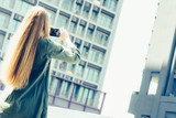 Young blond woman with smartphone in front of skyscrapers - 243945038