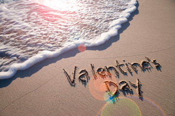 Valentine's Day message handwritten on smooth sand beach with lens flare above oncoming wave