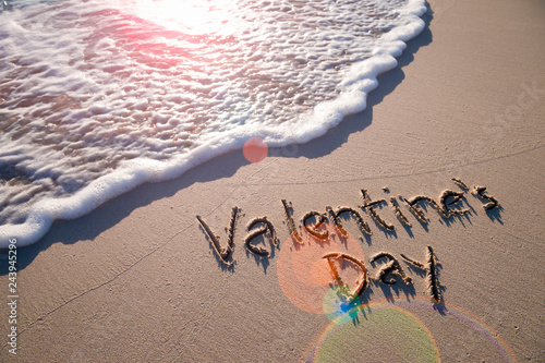 Valentine's Day message handwritten on smooth sand beach with lens flare above oncoming wave  - 243945296