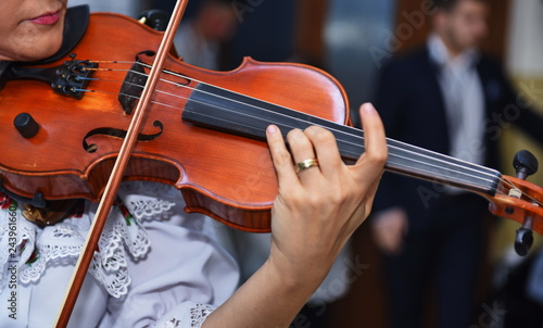 Close view of girls hand on violins strings - 243961660