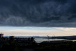 A dark storm cloud over a Saint John city in New Brunswick, Canada. White cloud and blue sky visible in the distance. City is very dark because of the cloud.