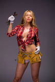 Young sexy girl in work clothes with a large wrench - 243994062