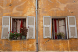 White shuttered windows in an old crumbling yellow wall in Menton, south eastern France - 243995495