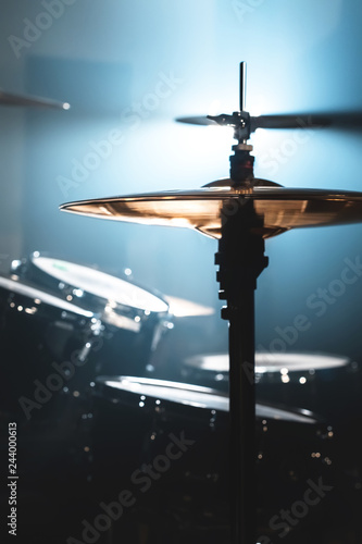 Close-up Drum set in a dark room against the backdrop of the spotlight. Atmospheric background symbol of playing rock or jazz drums. Copper plates on a cold background - 244000613