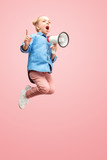 Beautiful young child teen girl jumping with megaphone isolated over pink background. Runnin girl in motion or movement. Human emotions,, facial expressions and advertising concept - 244015442