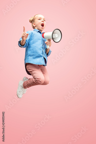 Beautiful young child teen girl jumping with megaphone isolated over pink background. Runnin girl in motion or movement. Human emotions,, facial expressions and advertising concept © master1305
