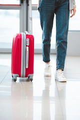 cropped view of woman walking with suitcase in airport