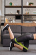 cropped view of sportswoman training with resistance band at home in living room