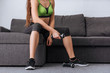 partial view of sportswoman sitting on sofa with dumbbells at home