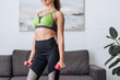 cropped view of smiling sportswoman holding dumbbells at home