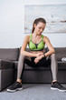 sportswoman sitting on couch and looking at watch at home