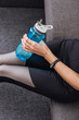cropped view of sportswoman with sport bottle sitting on couch at home