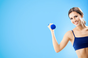 Woman in fitness wear with dumbbell, over blue © vgstudio