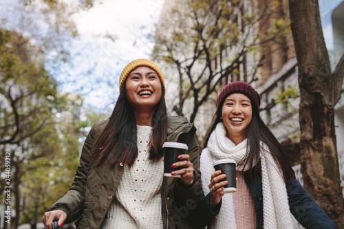 Wall mural Asian women walking on street holding coffee
