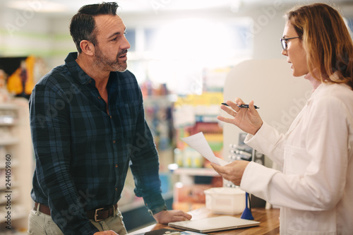 Pharmacist explaining a prescription to customer