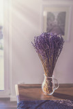 Fototapeta Lawenda - lavender in a glass on a table irradiated by the sun © Fischer Food Design