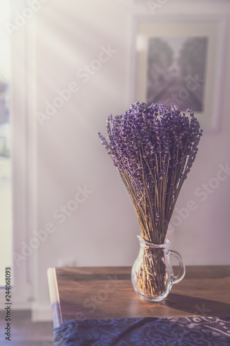 lavender in a glass on a table irradiated by the sun - 244068093