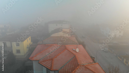 Panoramic aerial view of countryside scenario surrounded by fog, view from drone above the clouds - 244069060