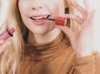 Happy cheerful woman using lips gloss