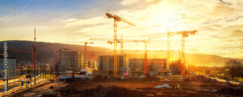 Large construction site including several cranes, with lots of gold sunlight - 244094814