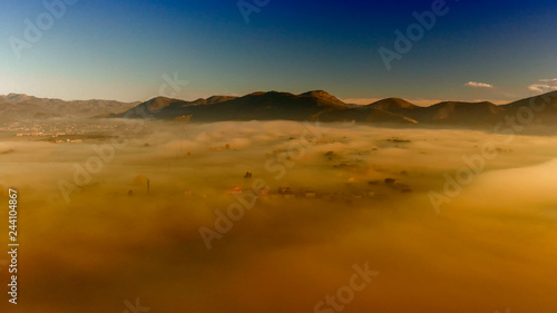 Panoramic aerial view of countryside scenario surrounded by fog, view from drone above the clouds - 244104867