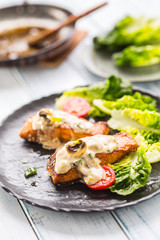 Delicious grilled roasted salmon fillets or steaks with mushroom sauce sesame tomatoes and lettuce salad © weyo