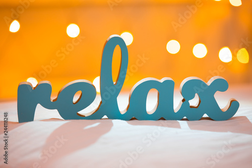Wall mural Wooden word relax on a bed with blurred lights bokeh background