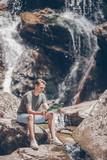 Man enjoying view of waterfall in gungle