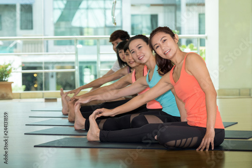 Wall mural Group of asian women and man practicing yoga, fitness stretching flexibility pose, working out, healthy lifestyle, wellness, well being