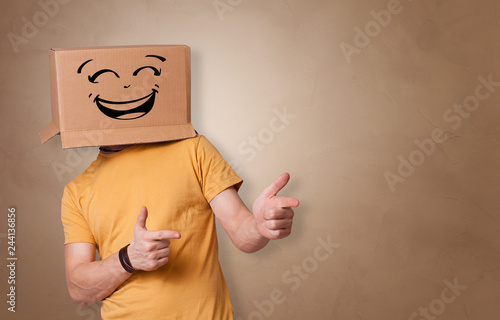 Leinwandbild Motiv Young man with happy face illustrated cardboard box on his head