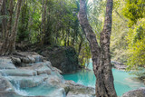 Jangle landscape with flowing turquoise water of Erawan cascade waterfall