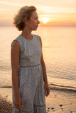 Natural portrait of a blonde woman in a dress near the sea in profile - 244159820