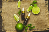Aromatherapy essential oil bottle with lime fruit and leaf mint.