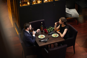 Young amorous dates sitting by table in luxurious restaurant, drinking red wine and talking before eating dinner