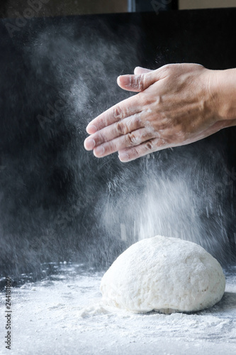 Fridge magnet making dough with flour by female hands