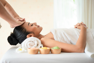 Relaxed woman lying on spa bed for facial and head massage spa treatment by massage therapist in a luxury spa resort