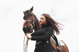 A happy girl communicates with her favorite horse. The girl loves animals andhorseback riding - 244184895