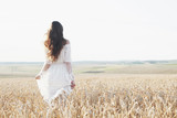 Beautiful girl in white dress running on the autumn field of wheat at sunset time - 244185811