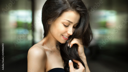 Wall mural Beautiful shy brunette woman smiling outdoors on city street. Natural beauty concept