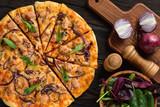 Homemade tuna and mozzarella pizza on wooden background.