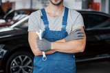 Hands of car mechanic with wrench in garage - 244203047